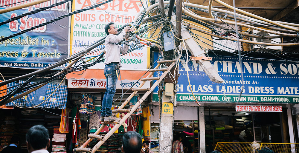 A view of disordered power lines and an engineer at work, Delhi, India